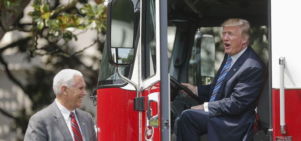 """Presiden Donald Trump, didampingi  Wakil Presiden Mike Pence, duduk di dalam sebuah kabin sebuah firetruck saat acara  """"Made in America,"""" yang menampilkan barang-barang produk dari  masing-masing 50 negara bagian AS, pada Senin, tanggal 17 Juli 2017, di sisi selatan halaman  Gedung Putih di Washington. (AP Photo / Pablo Martinez Monsivais)"""