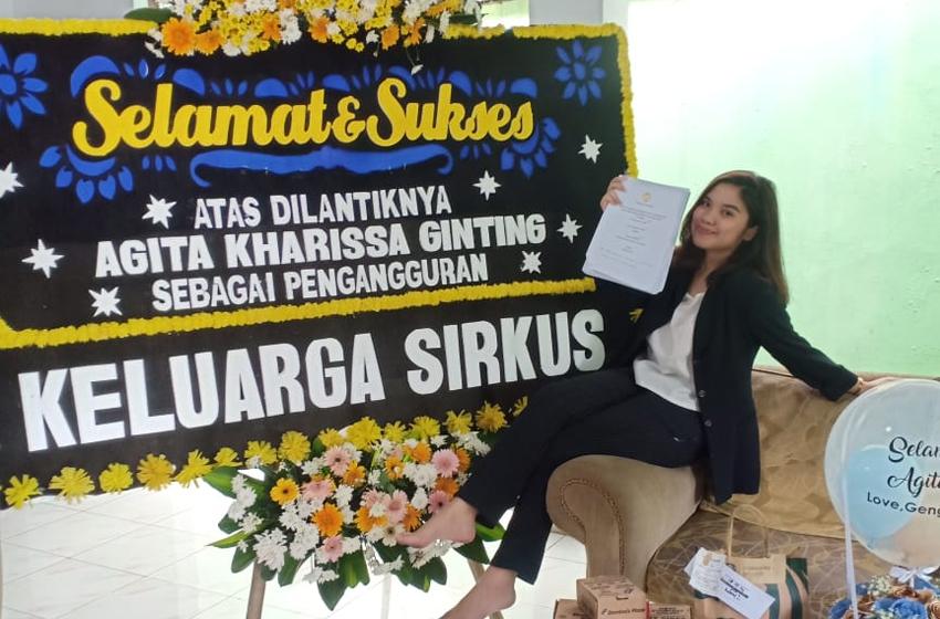 Agita Kharrisa Ginting dan bunga papan kiriman temannya. (foto: melva)